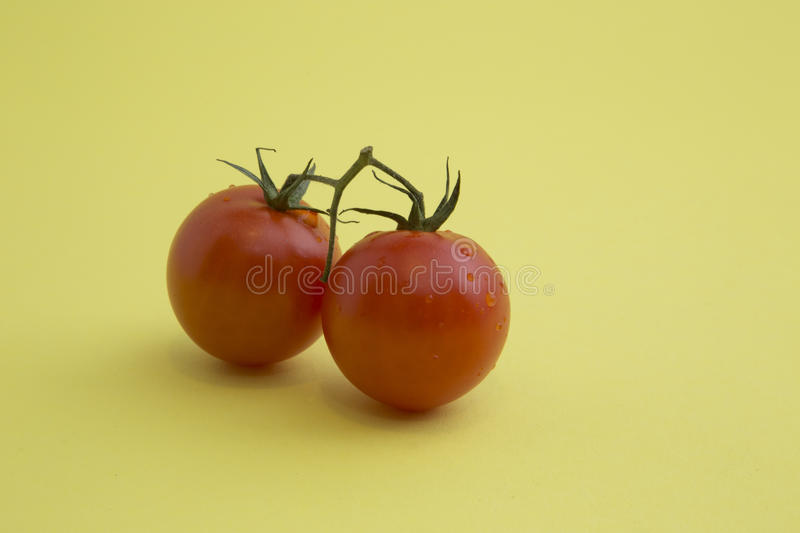 Cherry tomatoes. Two cherry tomatoes with waterdrops on a yellow background stock image