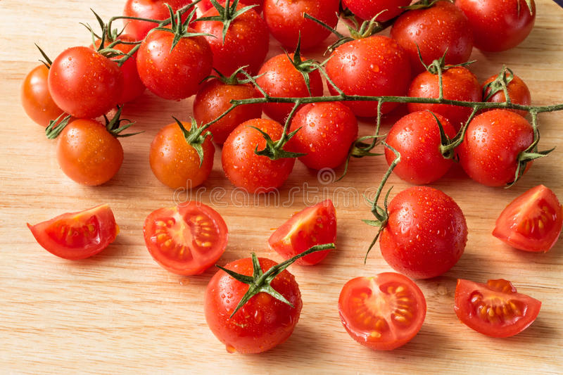 Cherry tomatoes - water drops- wood background royalty free stock photos