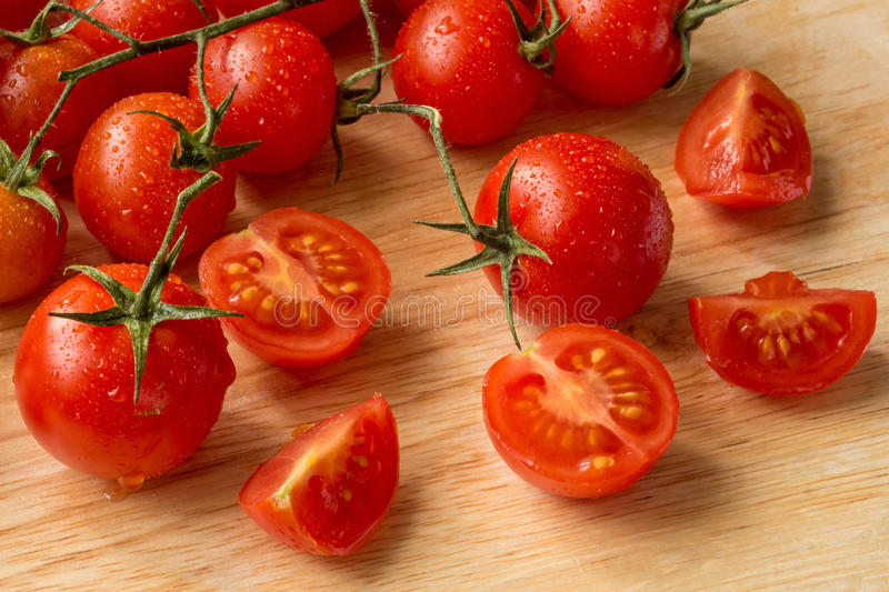 Cherry tomatoes - water drops- wood background royalty free stock image