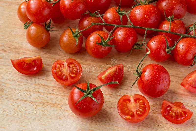 Cherry tomatoes - water drops- wood background royalty free stock photo