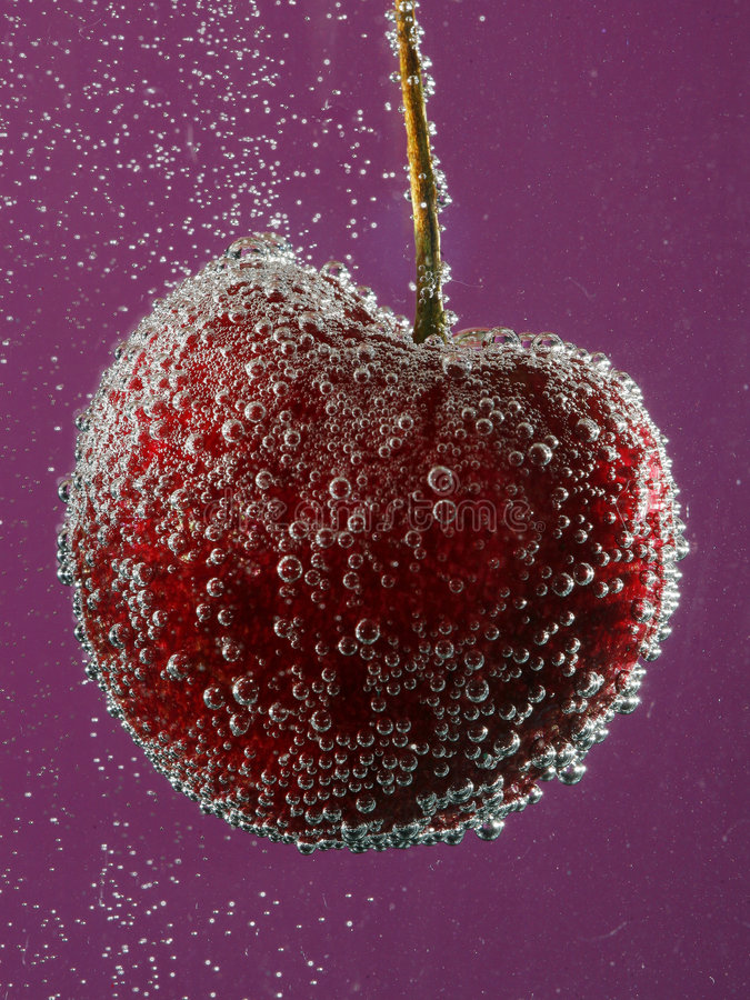 Cherry in water with bubbles. A red cherry submerged in water, covered with small bubbles, purple background stock photography