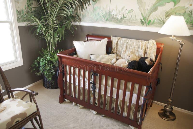 Cherry wood baby crib in nursery interior. stock image