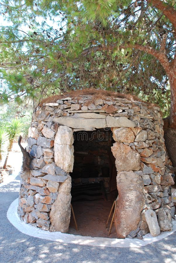 Chersonissos,塞浦路斯,希腊- 31 07 2013年:从石头收集的小屋在一棵绿色树下在克利特 向量例证