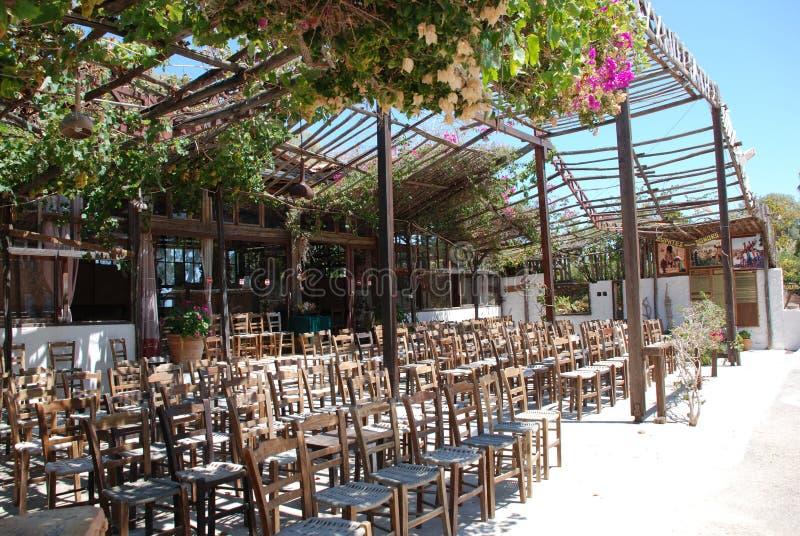 Chersonissos,塞浦路斯,希腊- 31 07 2013年:很多椅子在庭院里在夏天热的天空和花机盖下  库存照片
