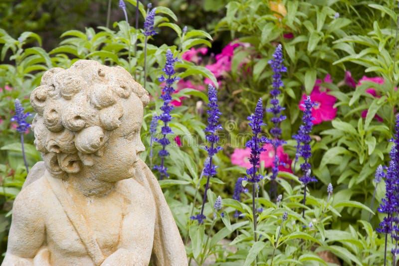 Cherub nel giardino di fiore fotografia stock