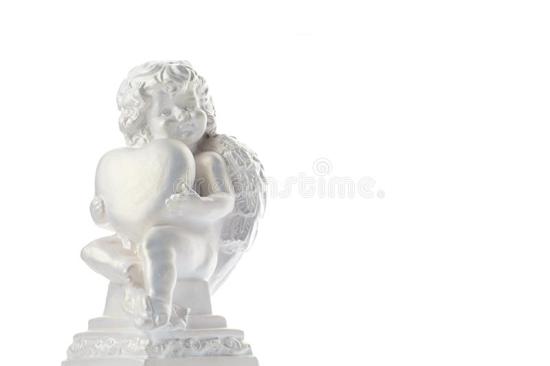 Cherub statue isolated on white background. Angel holds the heart. Love royalty free stock photography