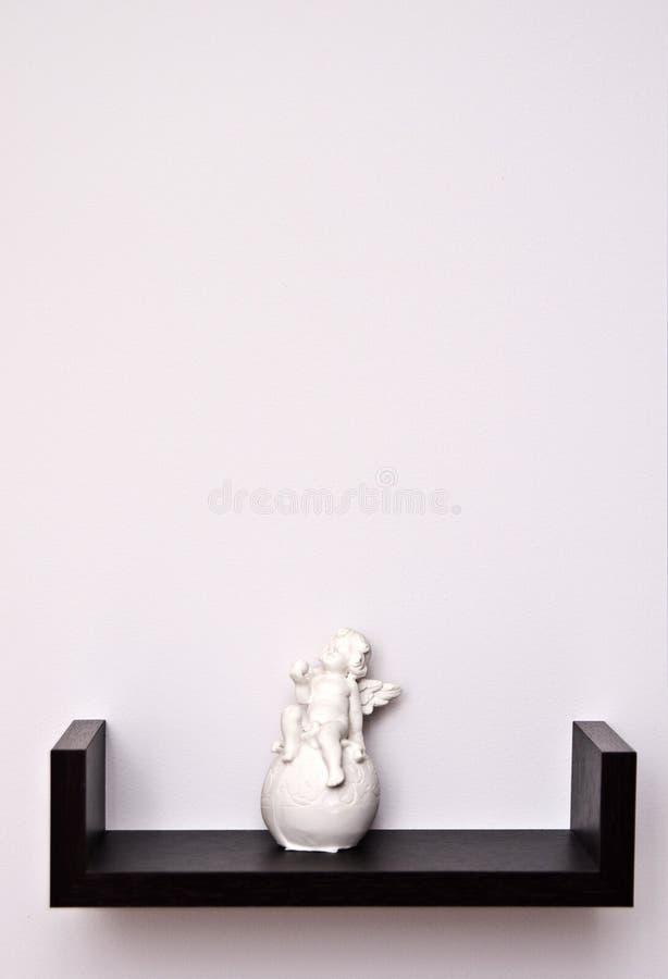 Cherub statue on shelf. Cherub statue on a shelf against a blank wall royalty free stock photo