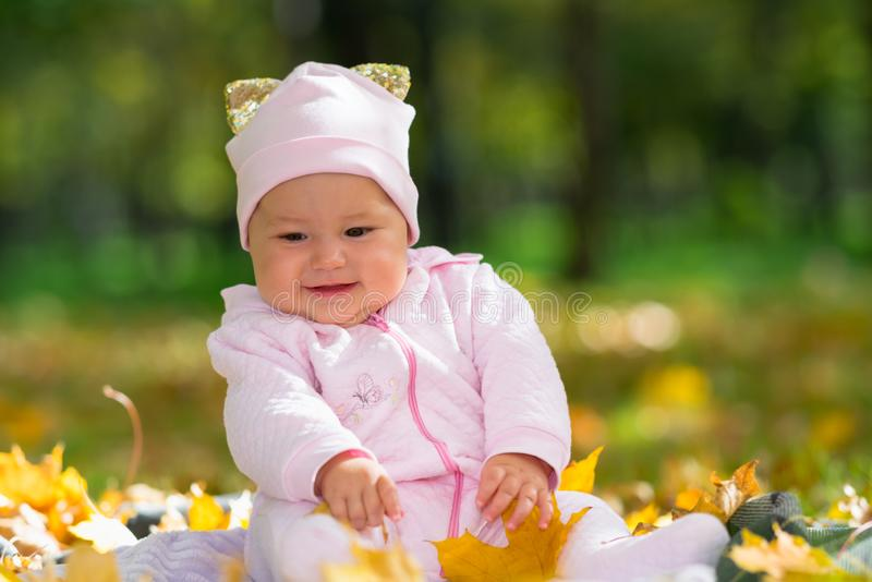 Cherubic baby girl playing with yellow leaves. Cherubic little baby girl playing with colorful leaves in an autumn park as she sits on a rug on the grass in a stock photography