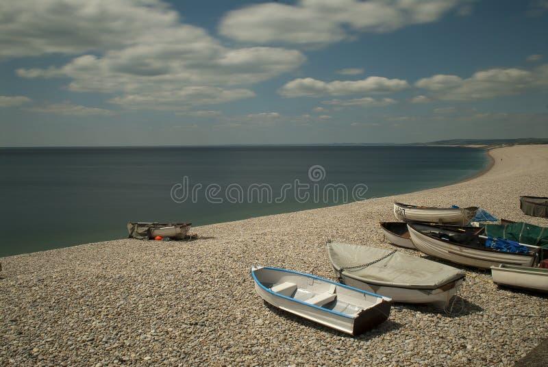 Chesil Beach. Rowing boats on Chesil Beach, Dorset, England under a cloudy blue sky stock photo