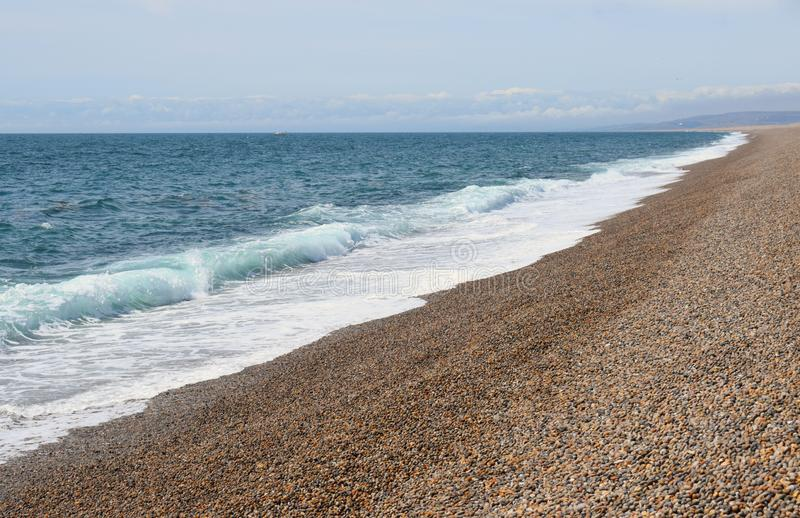 Chesil Beach in the UK. The view of the pebble beach and sea on the shore go Chesil Beach on the Jurassic Coast in the UK royalty free stock images