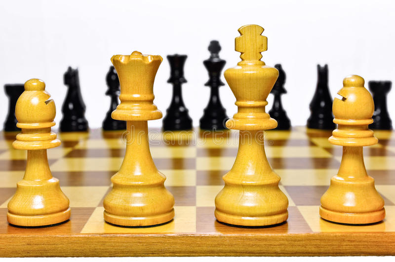 Chess. Pieces on board on white background. Focus on foreground. Shallow dof stock image