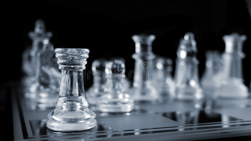 Chess -Alone in the Corner. Glass Chess Pieces on a Frosted Glass Chess Board royalty free stock photography