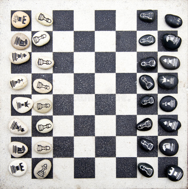 Chess board. A stone chess board with stone chess pieces royalty free stock images