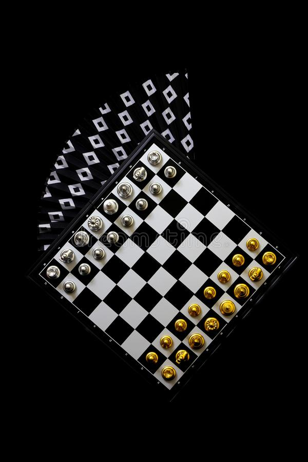 Chess board and pieces on black background with paper fan. Chess board with beautiful black and gold color pieces presented on black backdrop with a beautiful royalty free stock image