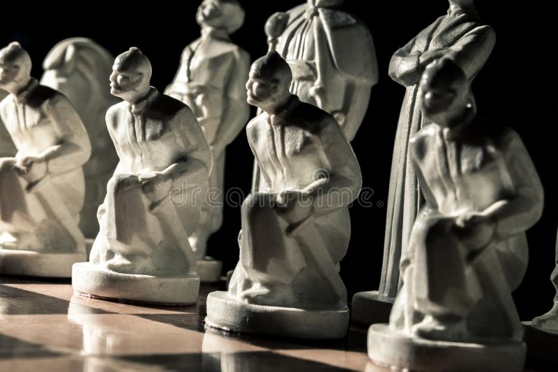Chess board. Beautiful white hand-made pawns among allied chess royalty free stock image