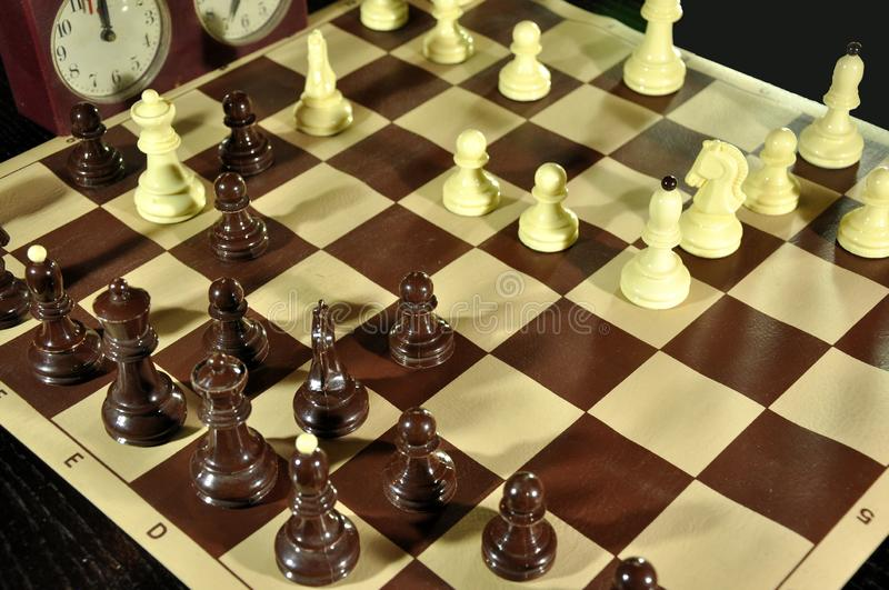 Chess board with black figures in focus and clock in black background. Chess board with figures when white win. Black king is in mat position royalty free stock photo