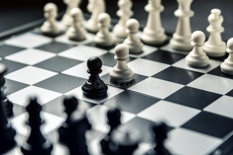 Chess board with black and white chess facing each other. White and black pawns go on the attack royalty free stock photography
