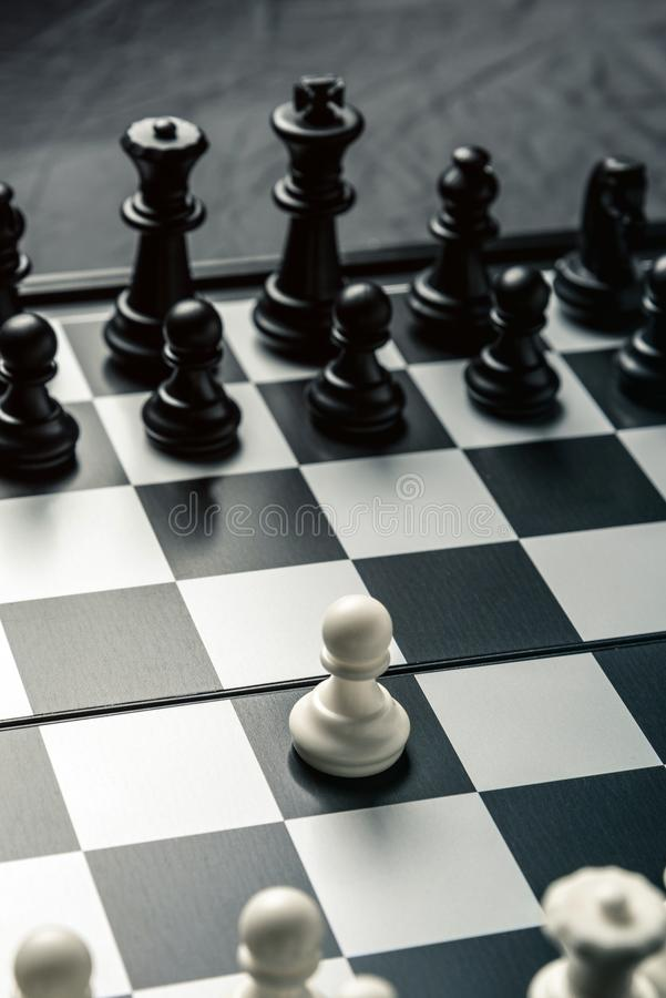 Chess board with black and white chess facing each other. White pawn goes on the attack royalty free stock photography