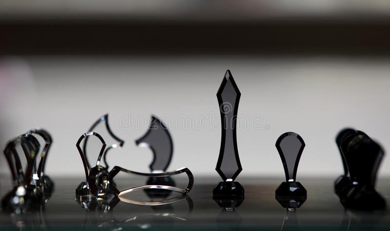 Chess board with chess pieces on grey background. Made of glass chess board with chess pieces on grey background stock photography