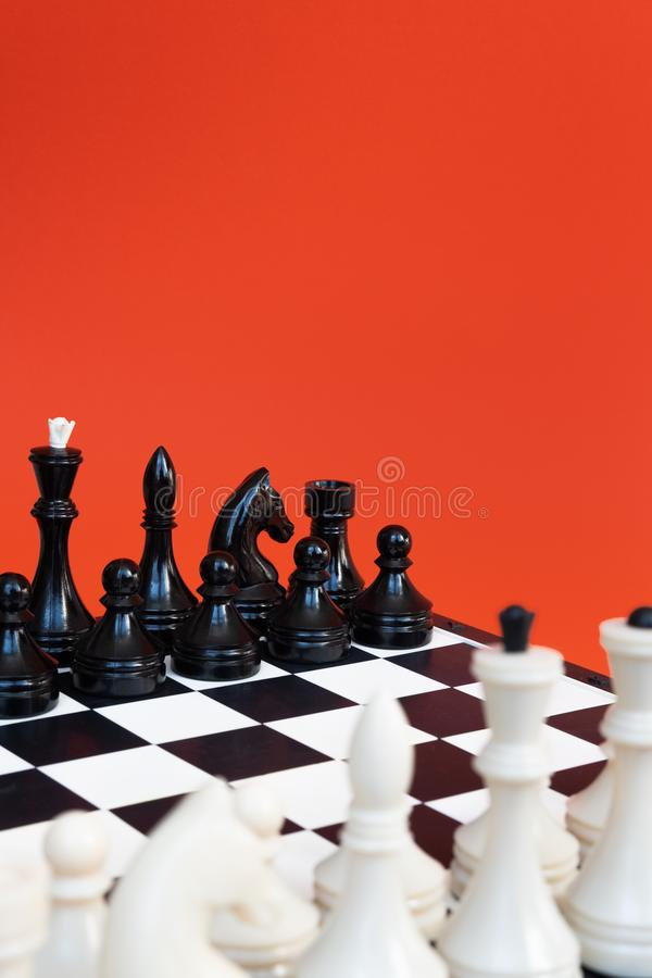 Chess board and chess figures on orange background top view copy space. Symbol of competition. Chess board and chess figures on orange background top view copy stock image