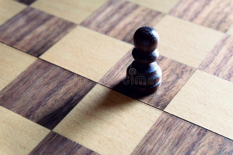 Chess board game. Black pawn stand outstanding under soft light. Leadership concept. Business winner royalty free stock image