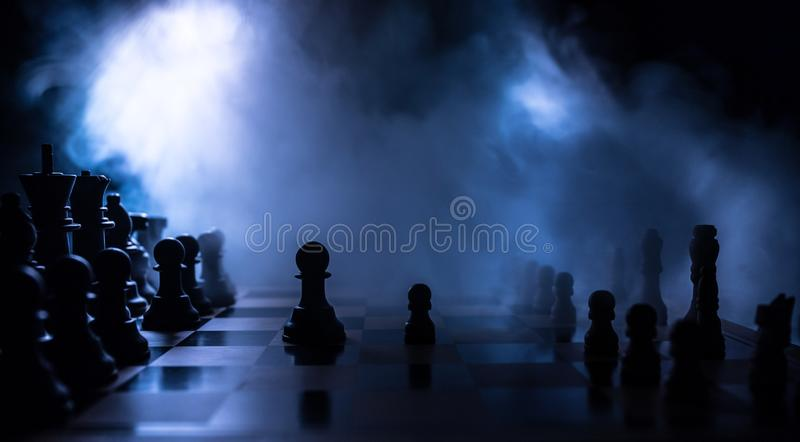 Chess board game concept of business ideas and competition. Chess figures on a dark background with smoke and fog. Selective royalty free stock photo