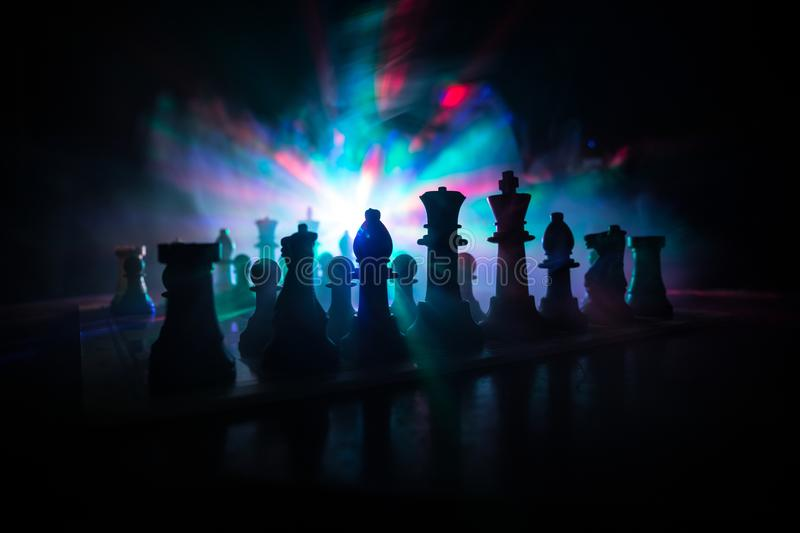 Chess board game concept of business ideas and competition. Chess figures on a dark background with smoke and fog. Selective royalty free stock photography