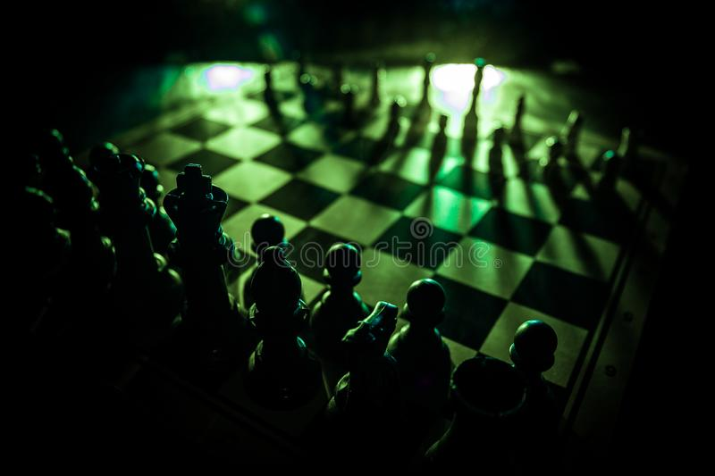 Chess board game concept of business ideas and competition. Chess figures on a dark background with smoke and fog. Selective focus stock photo