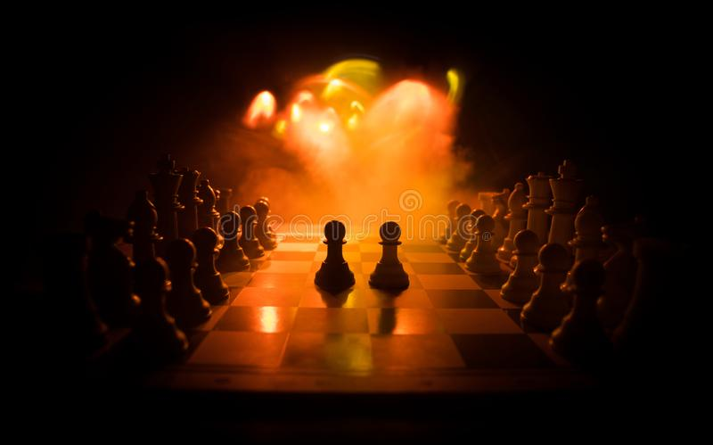 Chess board game concept of business ideas and competition. Chess figures on a dark background with smoke and fog. Selective focus royalty free stock photography