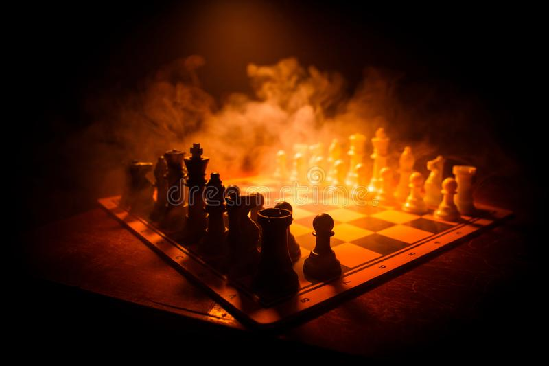 Chess board game concept of business ideas and competition. Chess figures on a dark background with smoke and fog. Selective stock photos