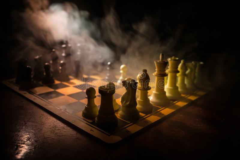 Chess board game concept of business ideas and competition. Chess figures on a dark background with smoke and fog. Selective focus royalty free stock photos