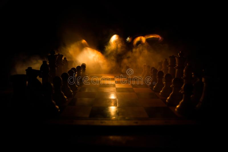 Chess board game concept of business ideas and competition. Chess figures on a dark background with smoke and fog. Selective focus stock photography