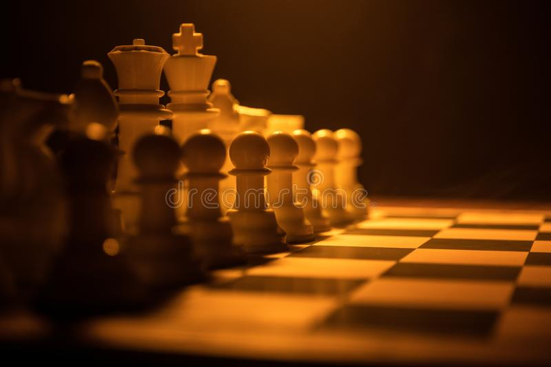 Chess board game concept of business ideas and competition. Chess figures on a dark background with smoke and fog. Selective focus royalty free stock images