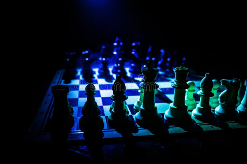 Chess board game concept of business ideas and competition. Chess figures on a dark background with smoke and fog. Selective focus royalty free stock image