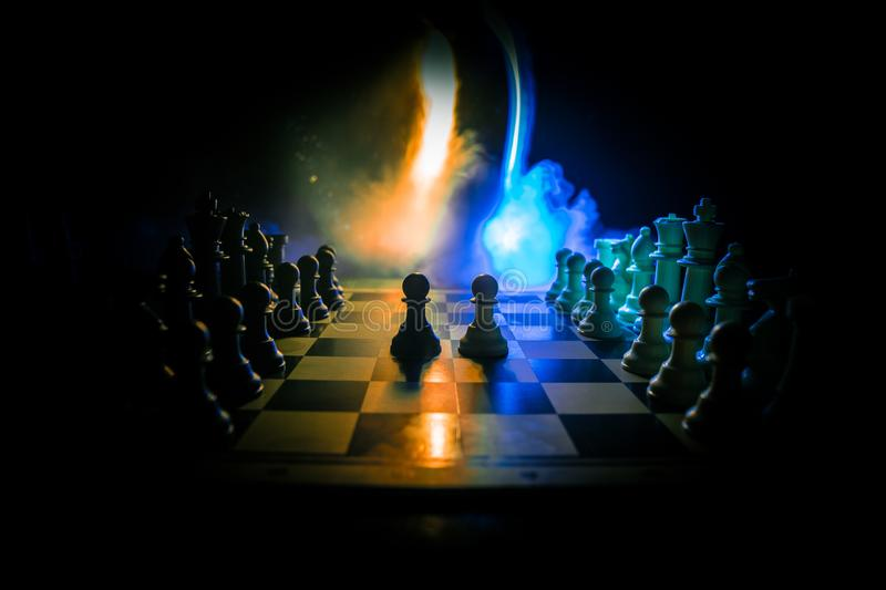 Chess board game concept of business ideas and competition. Chess figures on a dark background with smoke and fog. Selective focus stock image