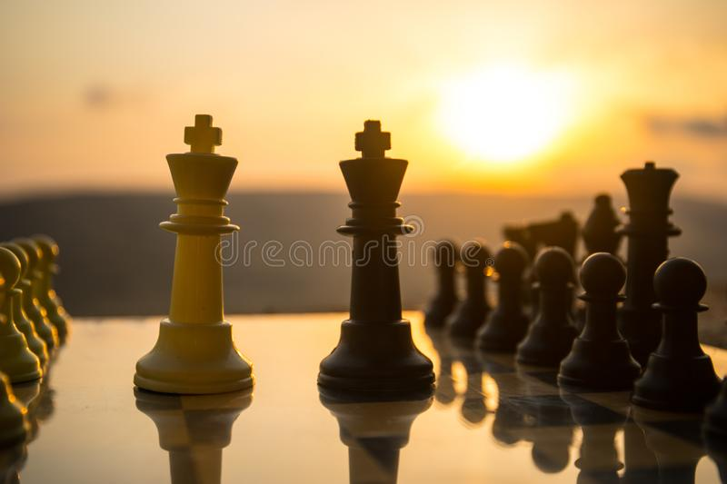 Chess board game concept of business ideas and competition and strategy ideas. Chess figures on a chessboard outdoor sunset backgr. Ound. Selective focus royalty free stock photos