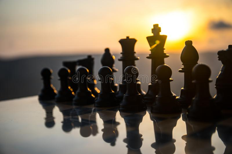 Chess board game concept of business ideas and competition and strategy ideas. Chess figures on a chessboard outdoor sunset backgr. Ound. Selective focus royalty free stock images