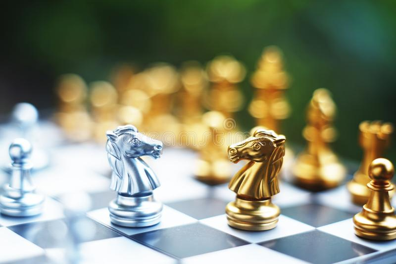 Chess board game. Fighting between silver and golden team. Business competitive and strategy planning concept. Copy space royalty free stock photos