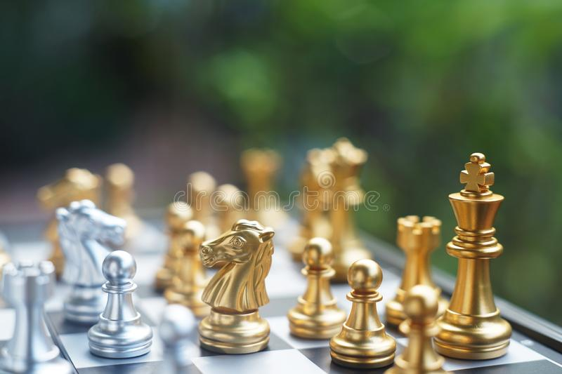 Chess board game. Fighting between silver and golden team. Business competitive and strategy planning concept. Copy space stock image