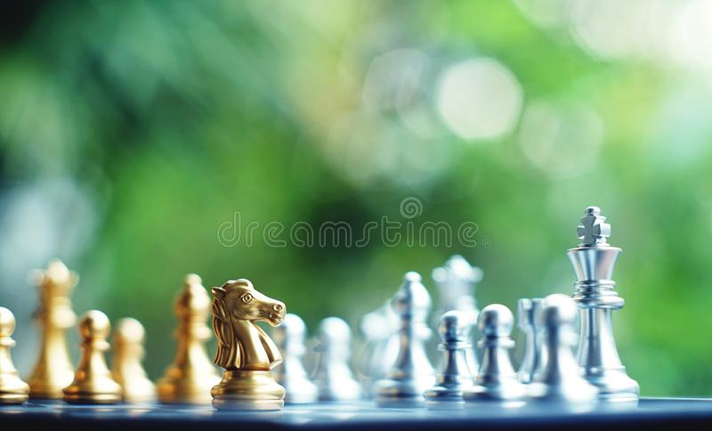 Chess board game. Fighting between silver and golden team. Business competitive and strategy planning concept. Copy space royalty free stock photo