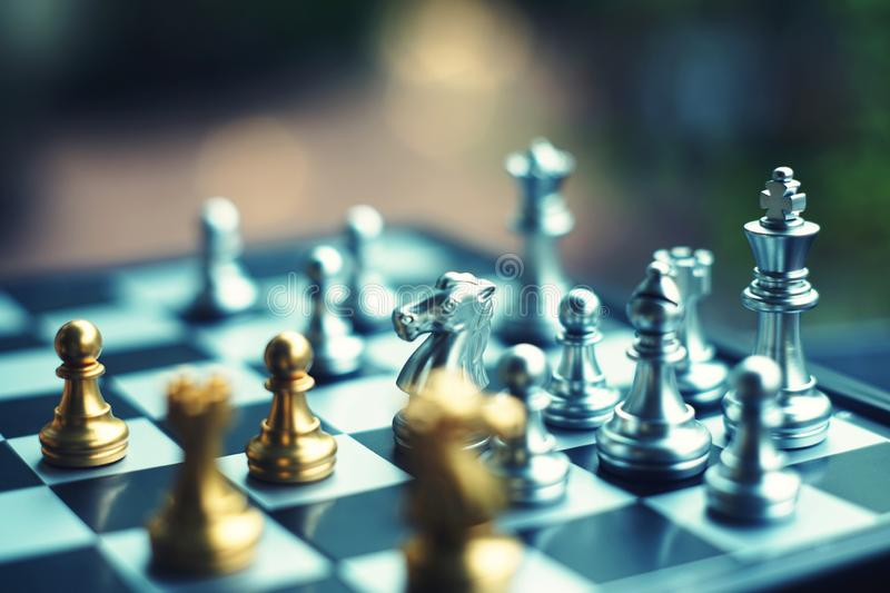 Chess board game. Fighting between silver and golden team. Business competitive and strategy planning concept. Copy space royalty free stock image