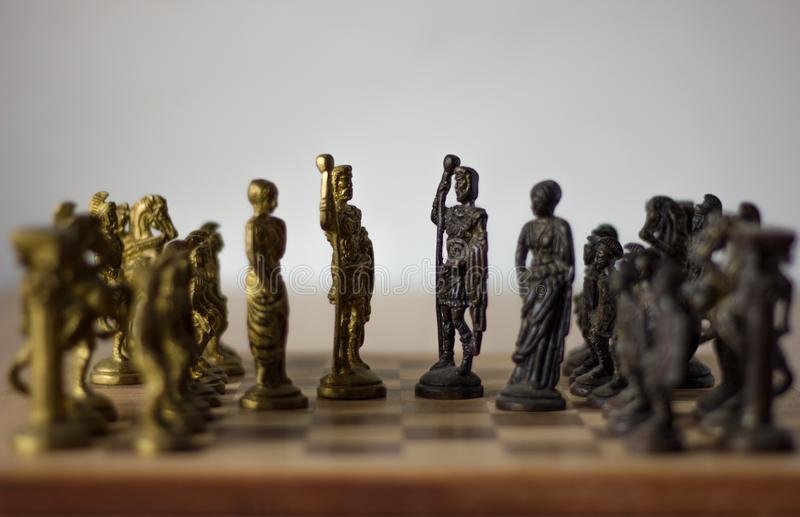 Chess board game, with kings and queens discussing for compromise, peace talks with  their army behind. Selective focus of chess figures royalty free stock photos