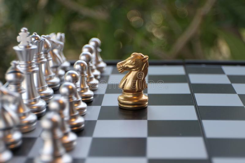Chess board game. A knight faces all the enemies. Leader with courage concept stock photography