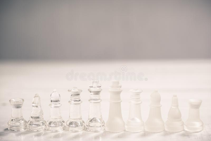 Chess board game made of glass, business competitive concept. Copy space white transparent transparency pieces king queen knight pawn rook hand finance stock photos