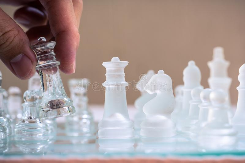 Chess board game made of glass, business competitive concept. Copy space white transparent transparency pieces king queen knight pawn rook hand finance royalty free stock photos