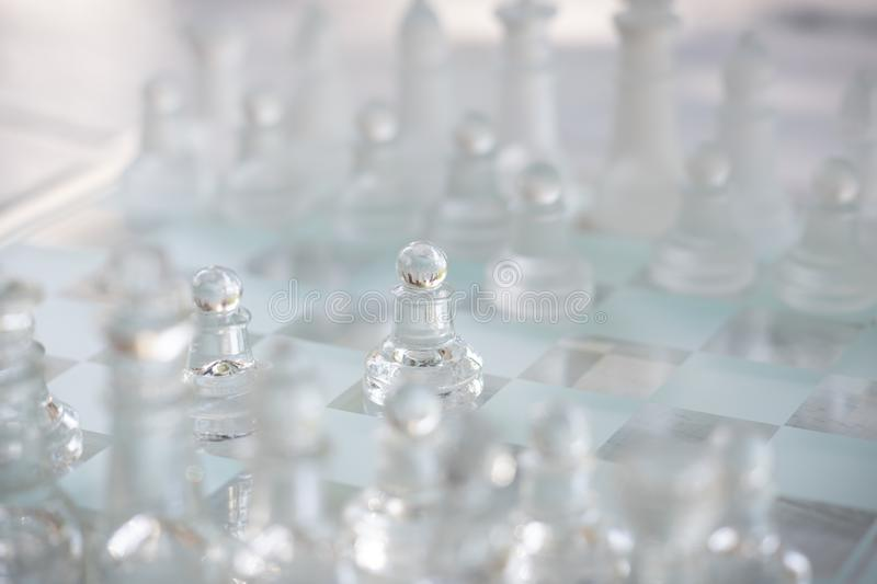 Chess board game made of glass, business competitive concept. Copy space, white, transparent, transparency, pieces, king, queen, knight, pawn, rook, hand stock images