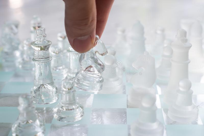 Chess board game made of glass, business competitive concept. Copy space white transparent transparency pieces king queen knight pawn rook hand finance royalty free stock photography