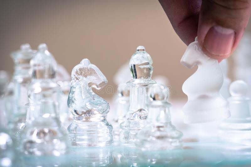 Chess board game made of glass, business competitive concept. Copy space white transparent transparency pieces king queen knight pawn rook hand finance stock photo