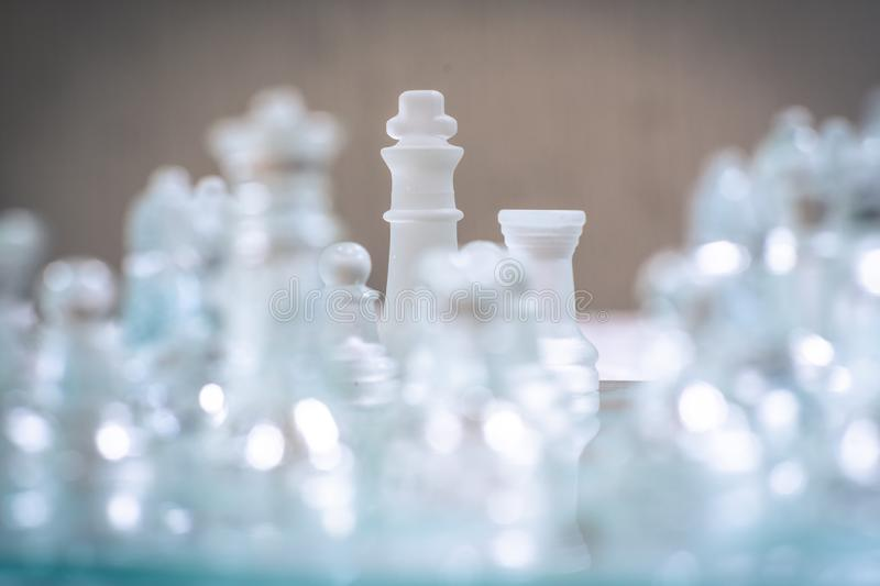 Chess board game made of glass, business competitive concept. Copy space white transparent transparency pieces king queen knight pawn rook hand finance royalty free stock photo