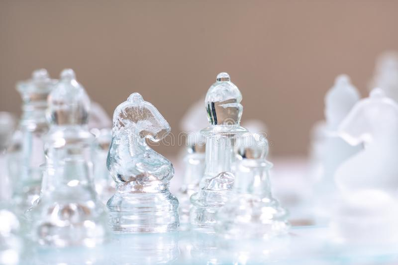 Chess board game made of glass, business competitive concept. Copy space white transparent transparency pieces king queen knight pawn rook hand finance stock image